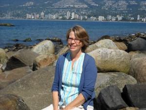 Joyce sitting on the rocks along the Vancouver shoreline